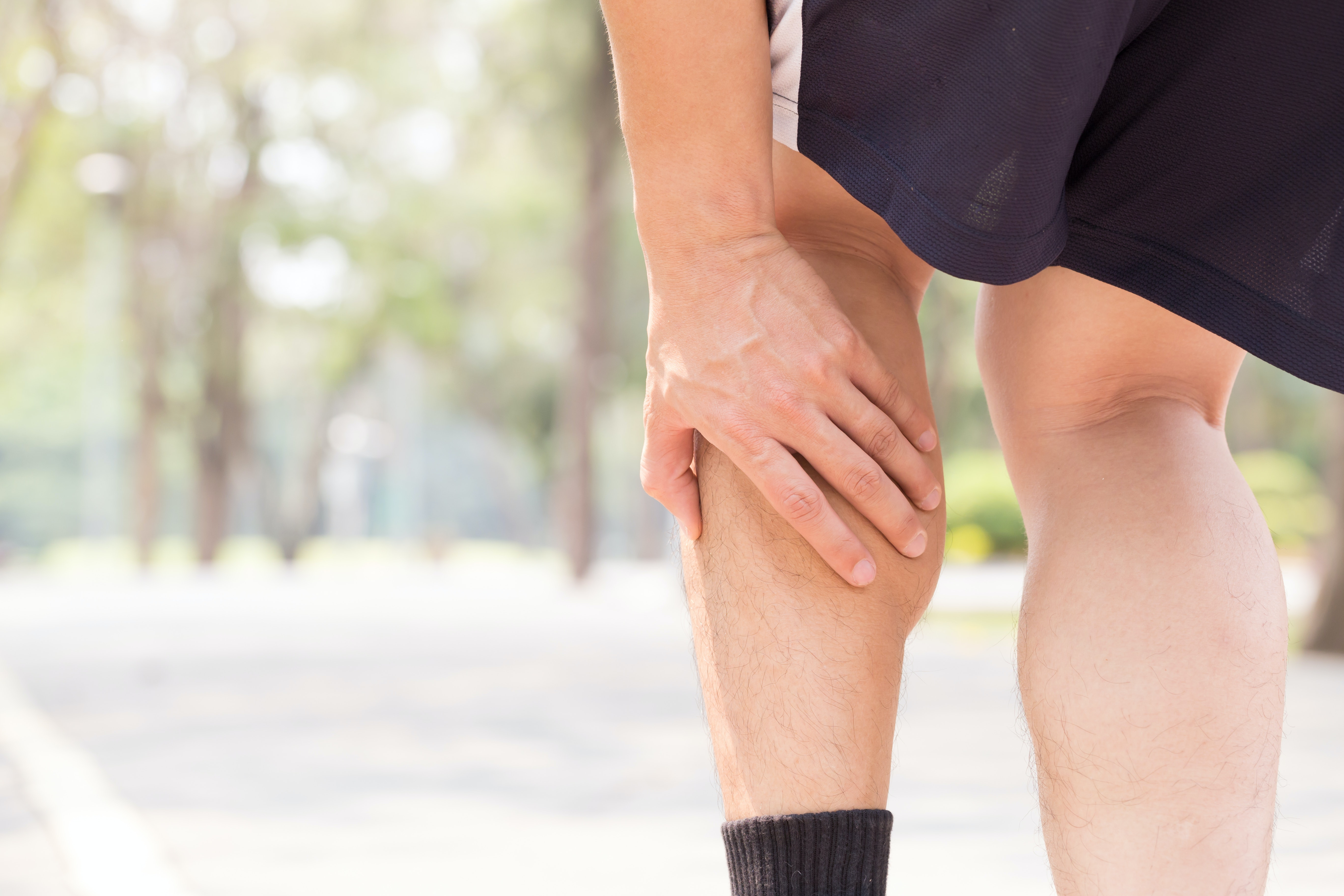 An image depicting a person suffering from calf pain symptoms