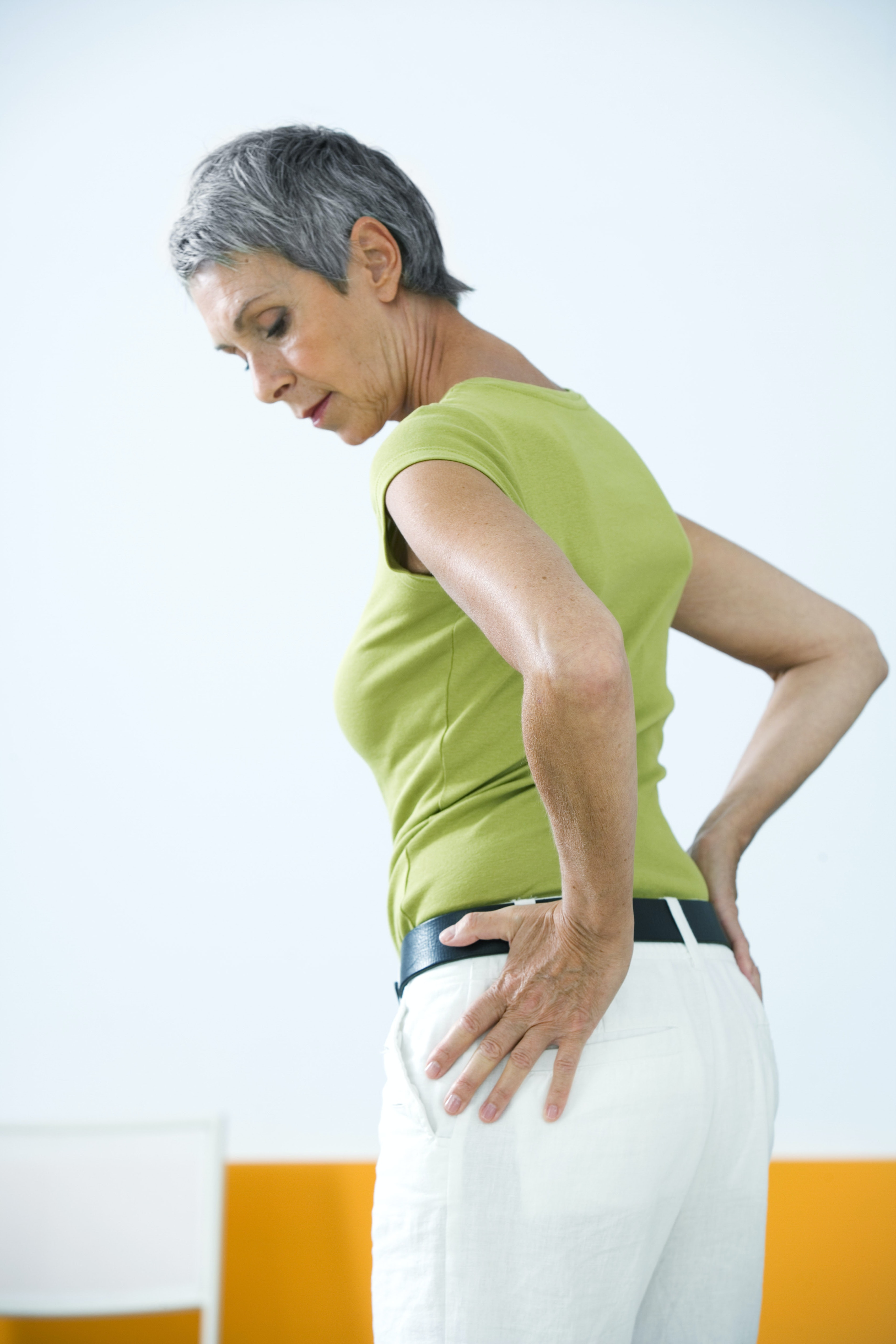 An image depicting a person suffering from dull, achy hip pain symptoms