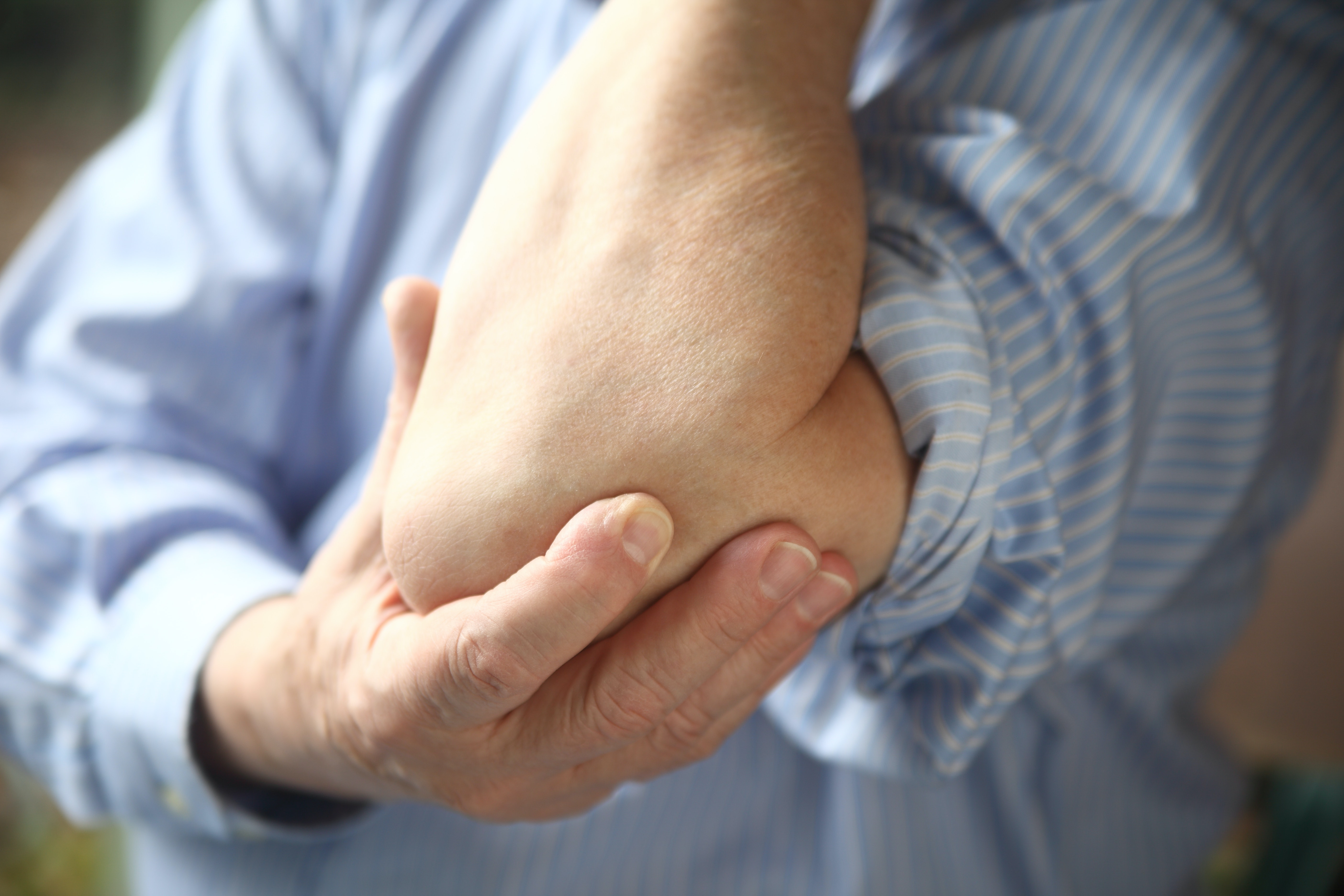 An image depicting a person suffering from elbow popping symptoms