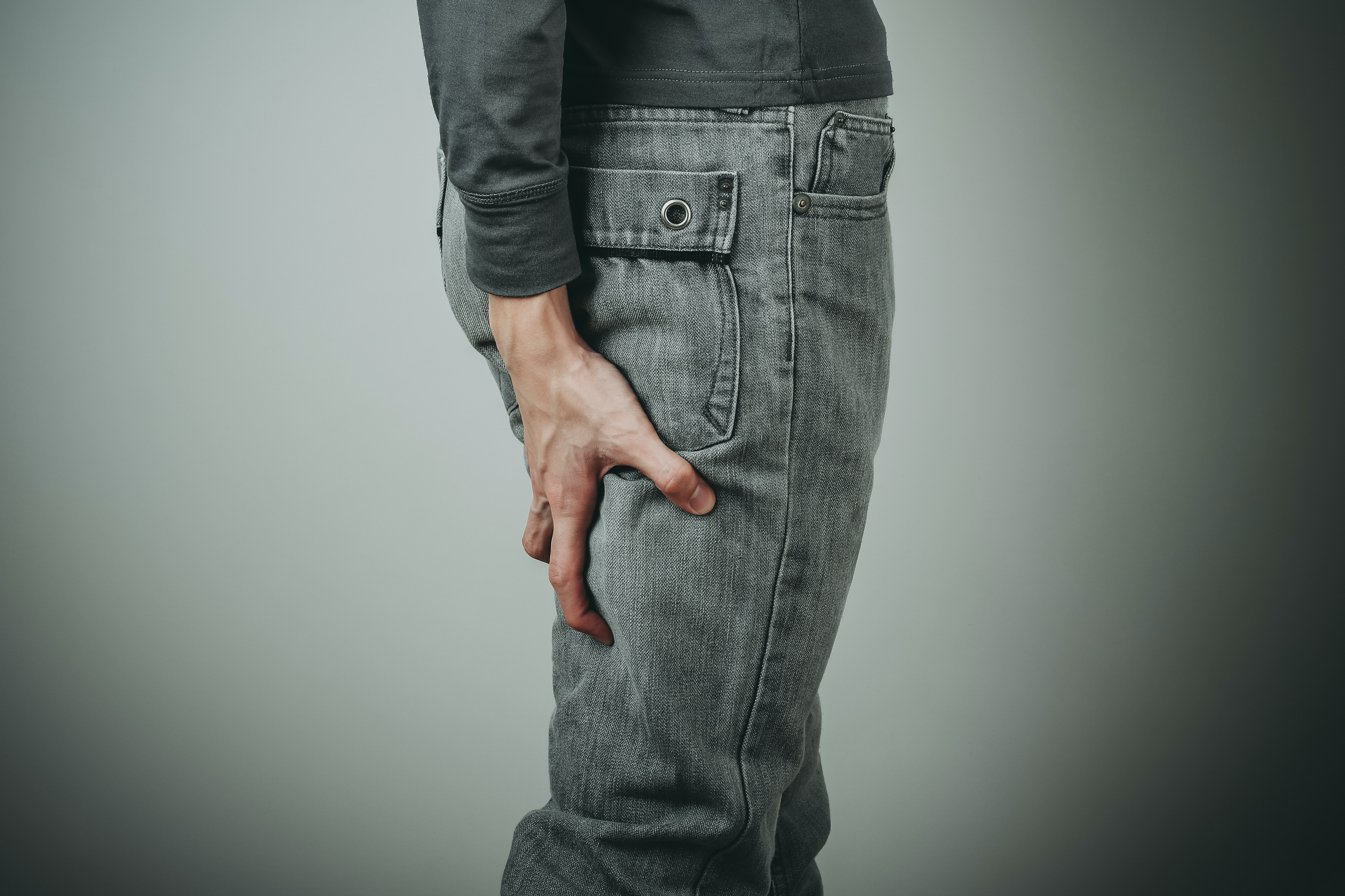An image depicting a person suffering from hamstring pain symptoms