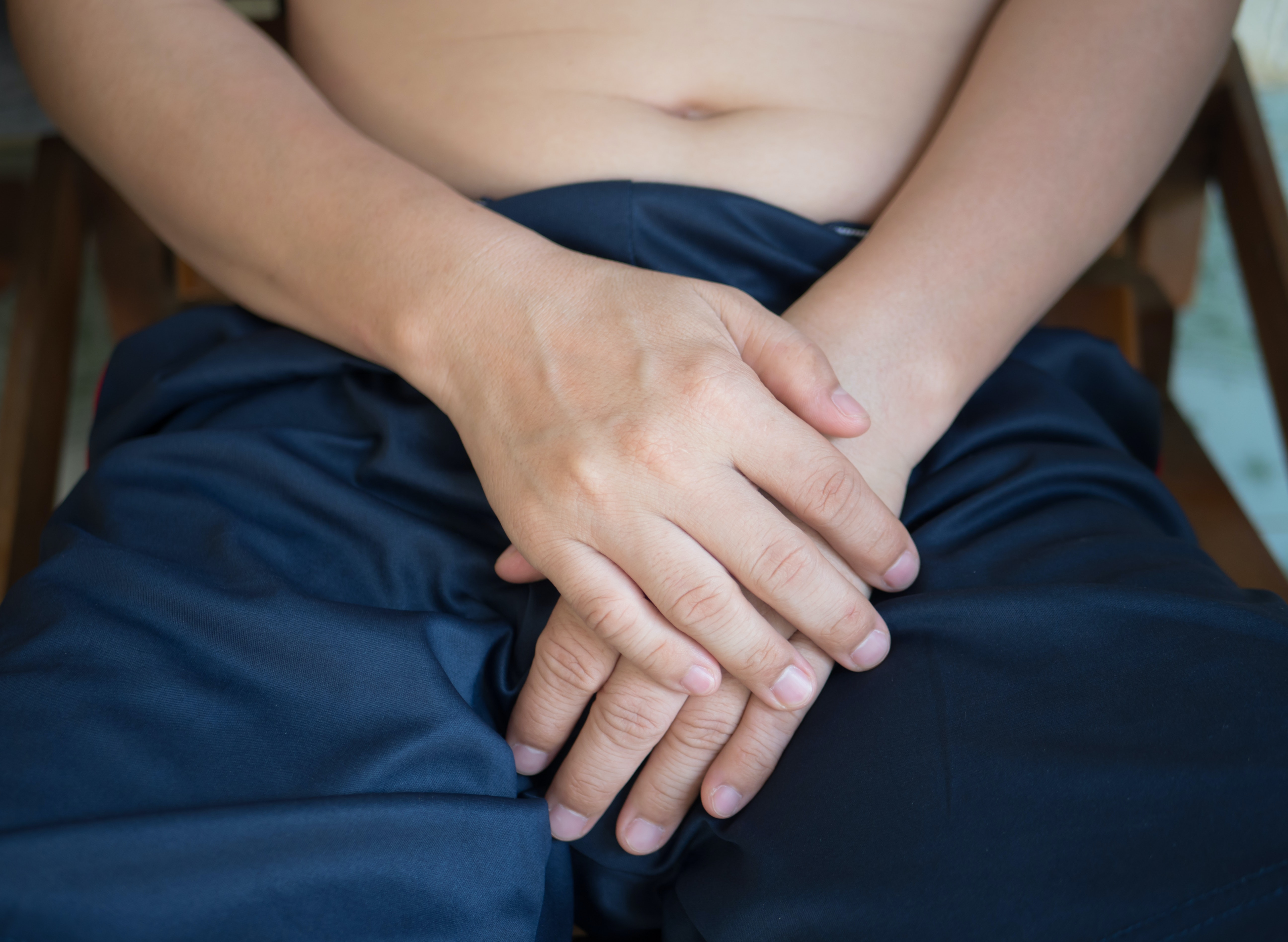 An image depicting a person suffering from hard groin lump symptoms