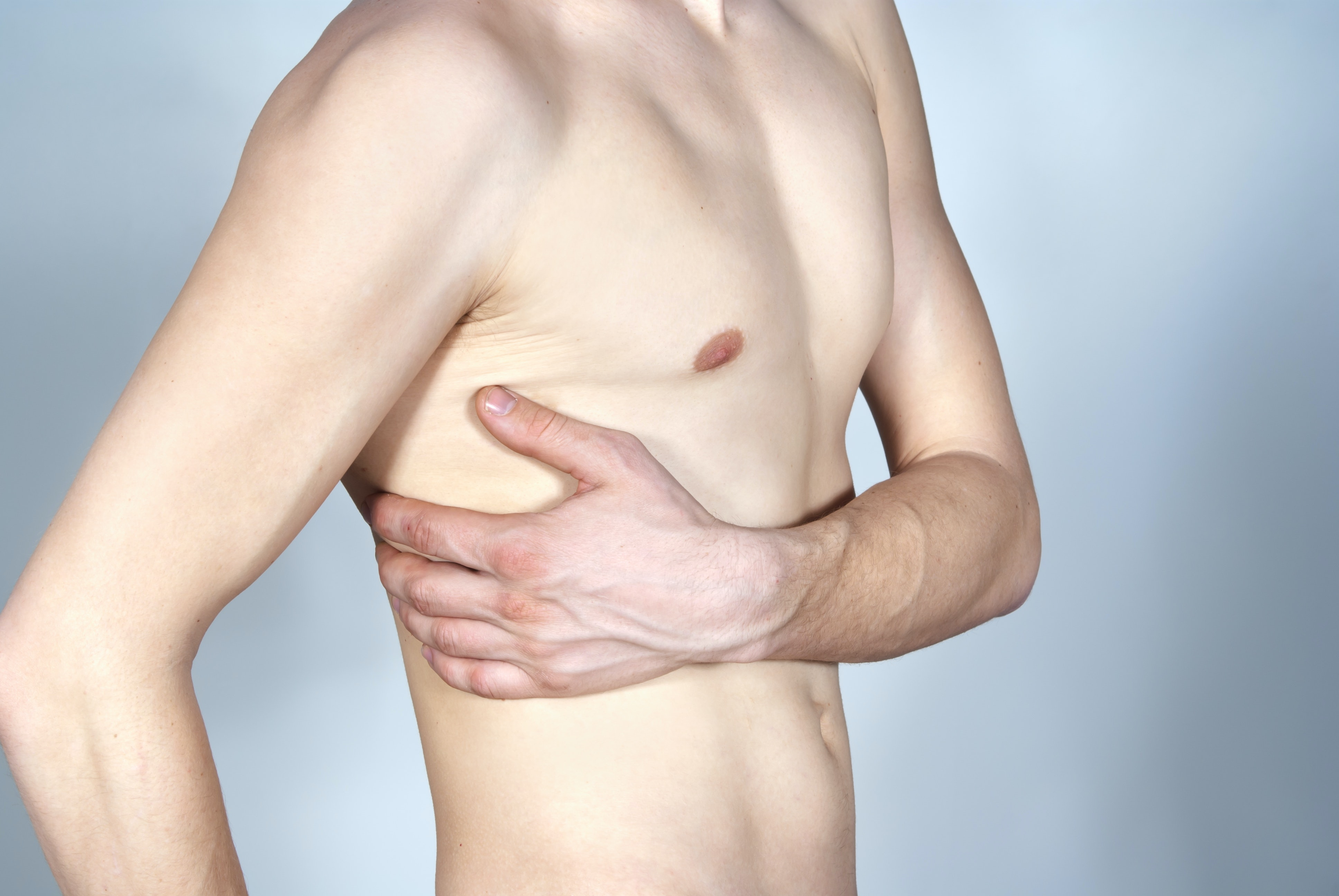 An image depicting a person suffering from mild rib pain symptoms