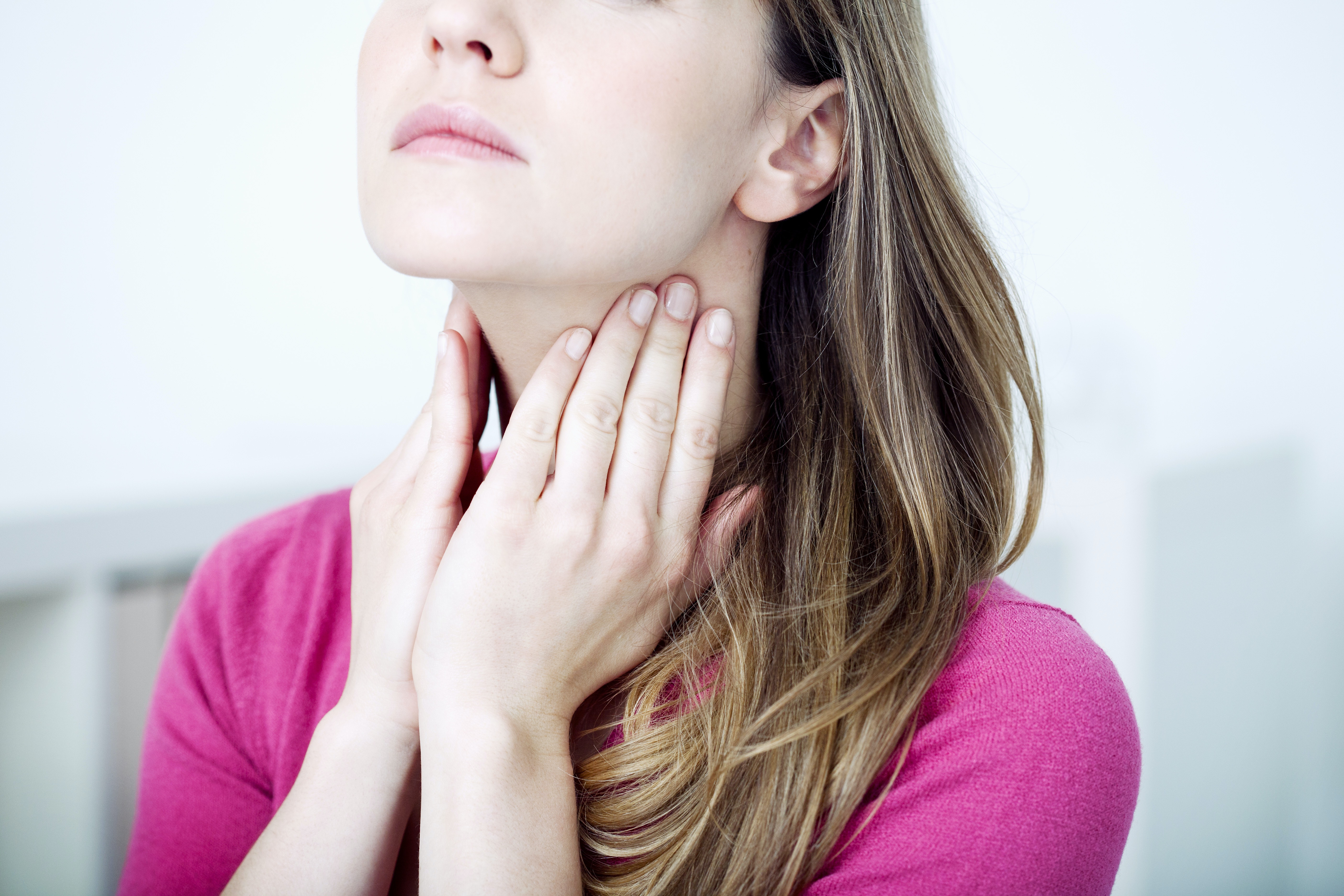 An image depicting a person suffering from mild sore throat symptoms