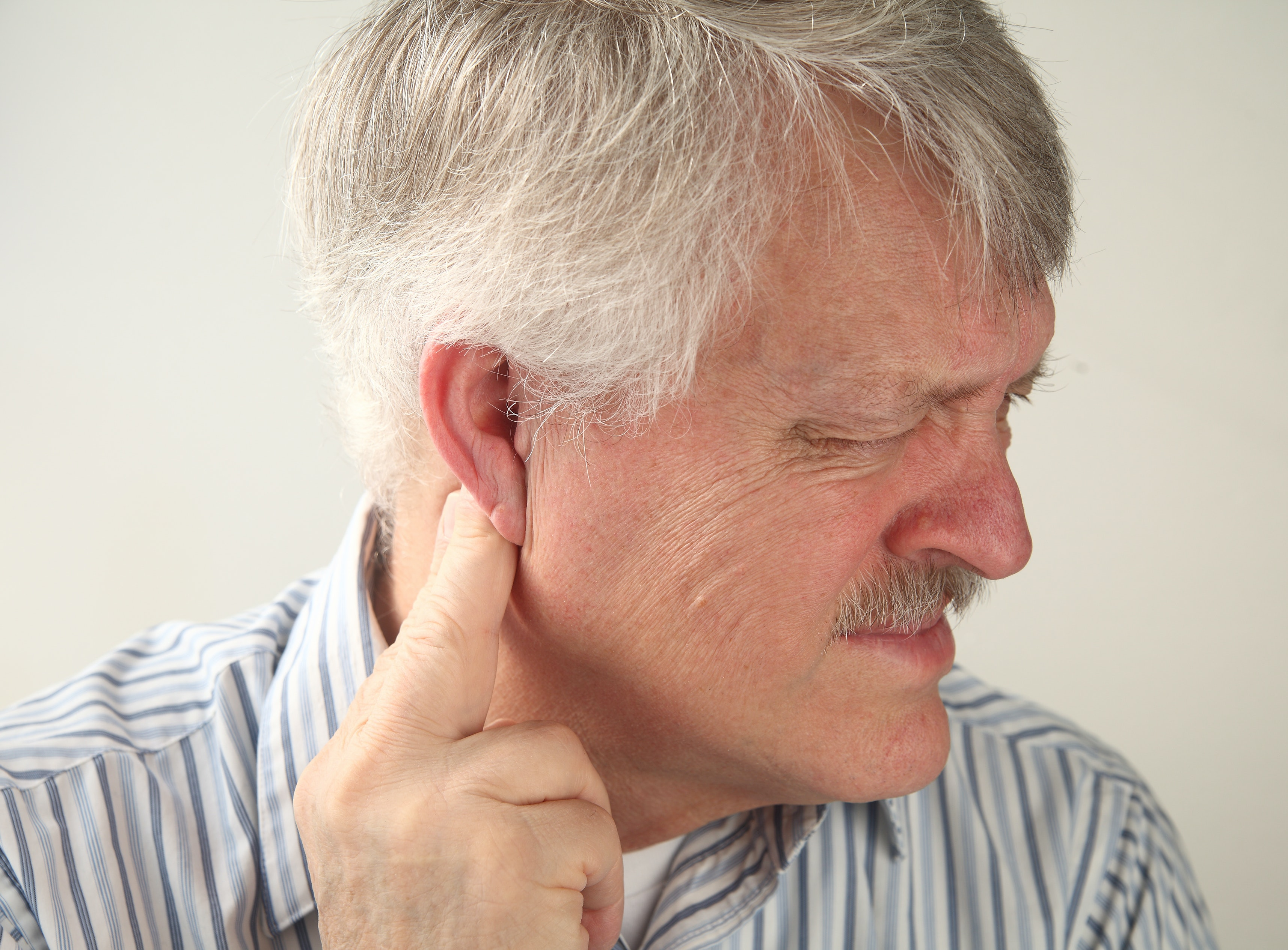 An image depicting a person suffering from pain behind the ear symptoms