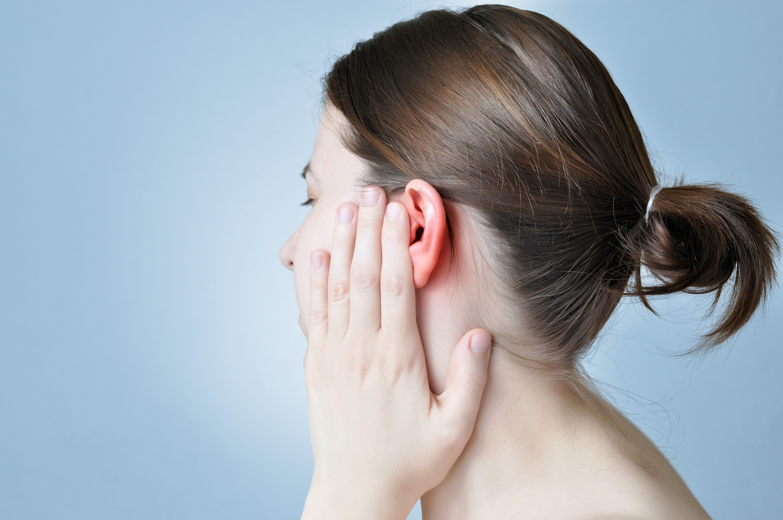 An image depicting a person suffering from pain in one ear canal symptoms