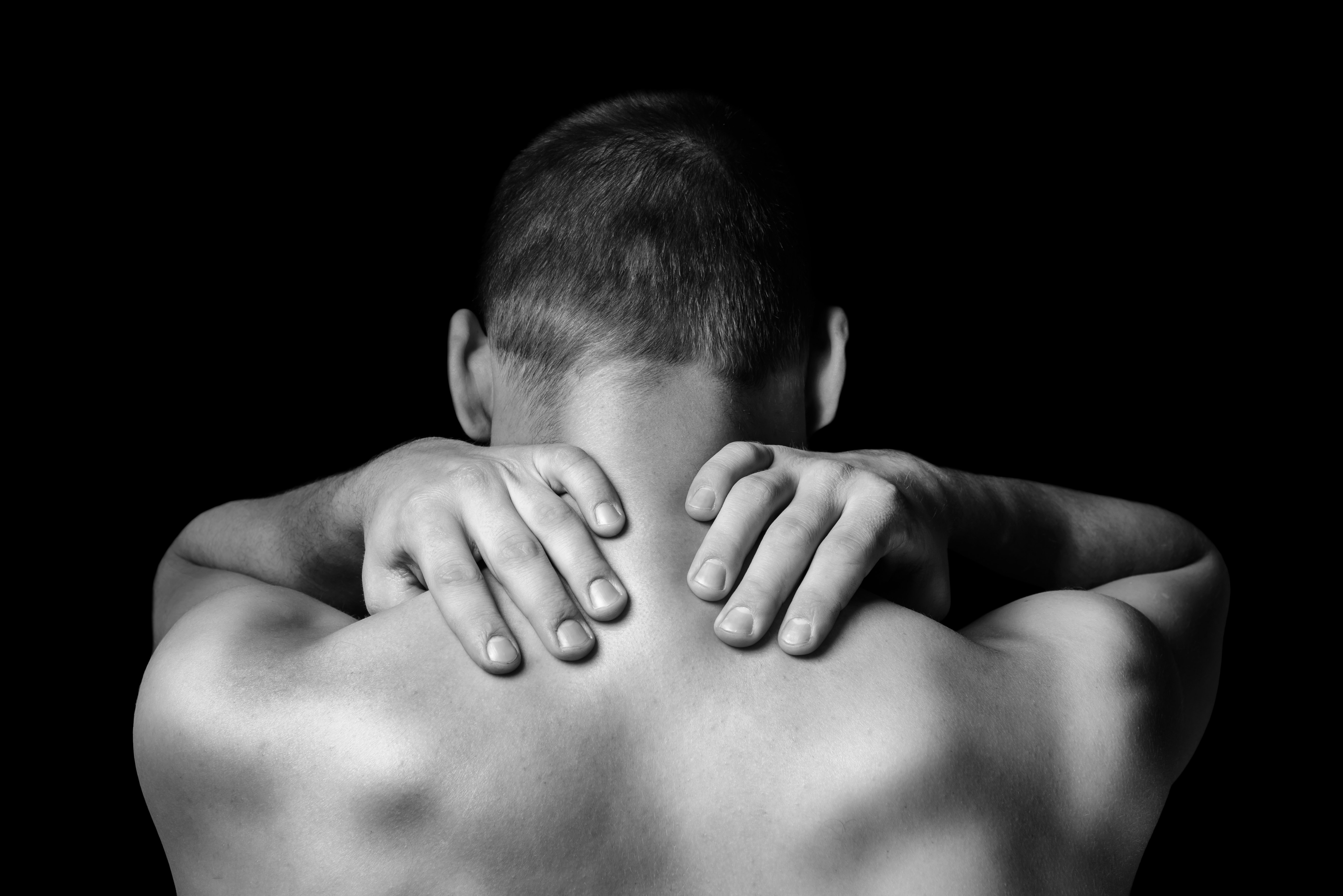 An image depicting a person suffering from pain in the back of the neck symptoms