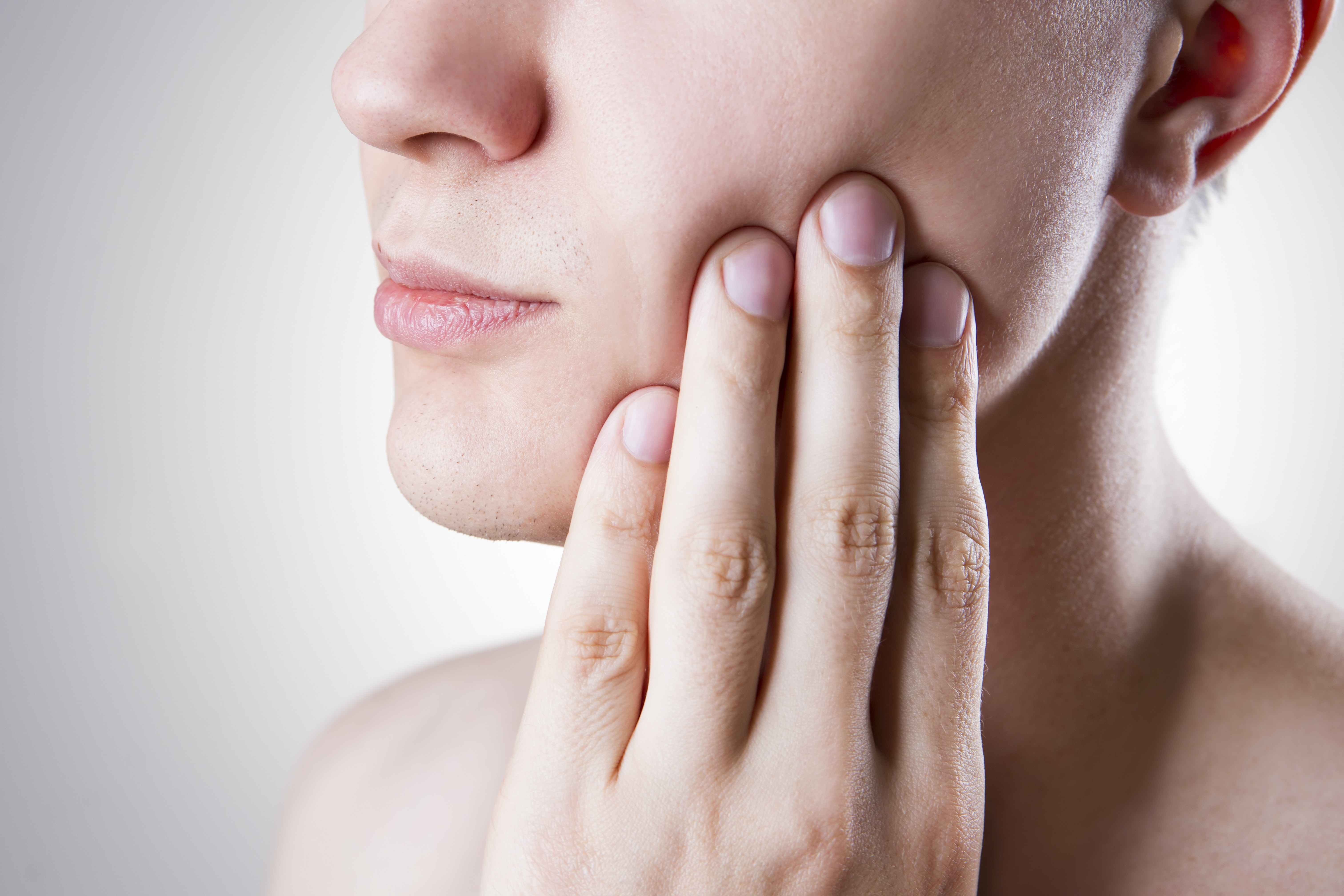 An image depicting a person suffering from pain in the lower pre-molar symptoms