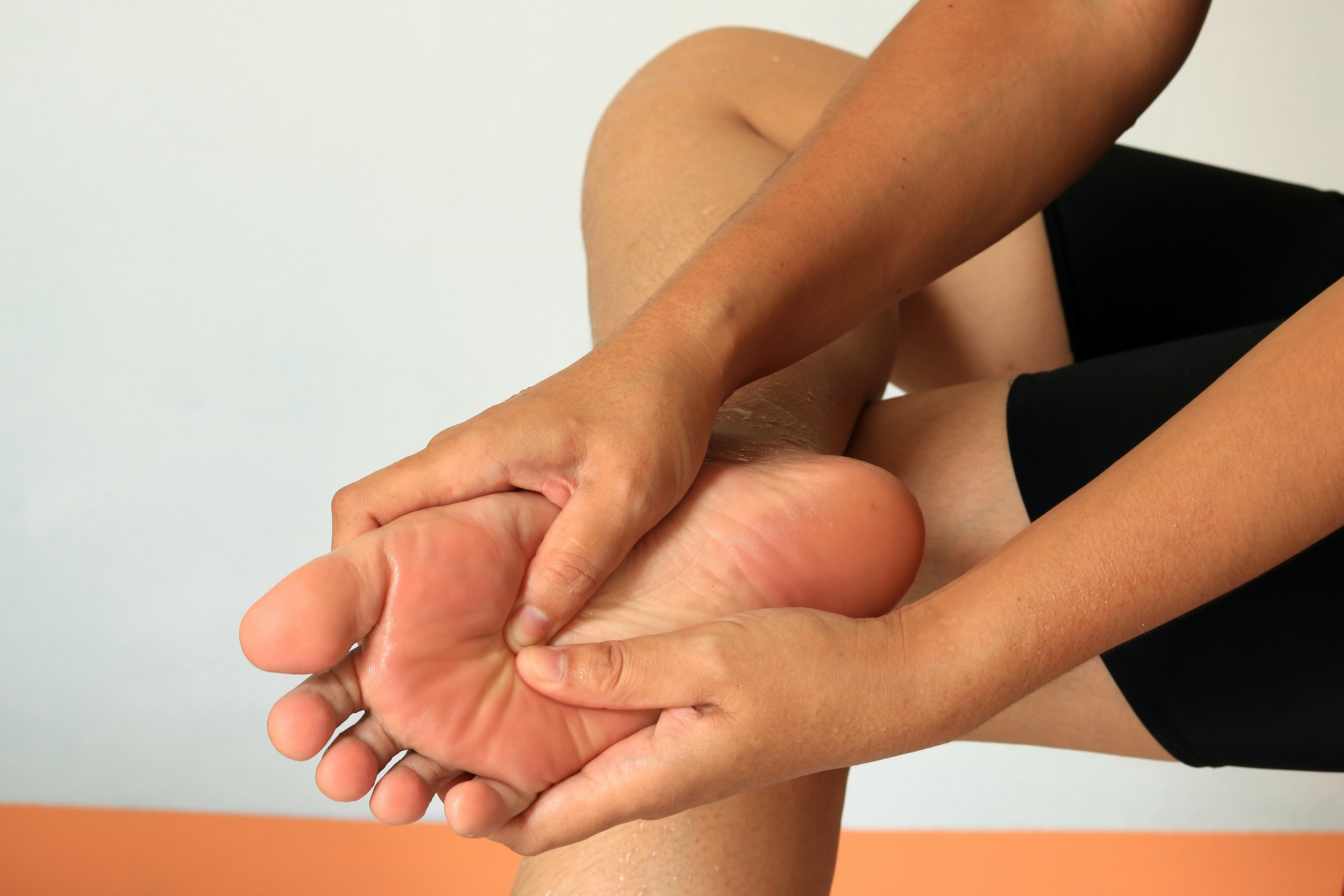 An image depicting a person suffering from pain in the middle of the foot symptoms