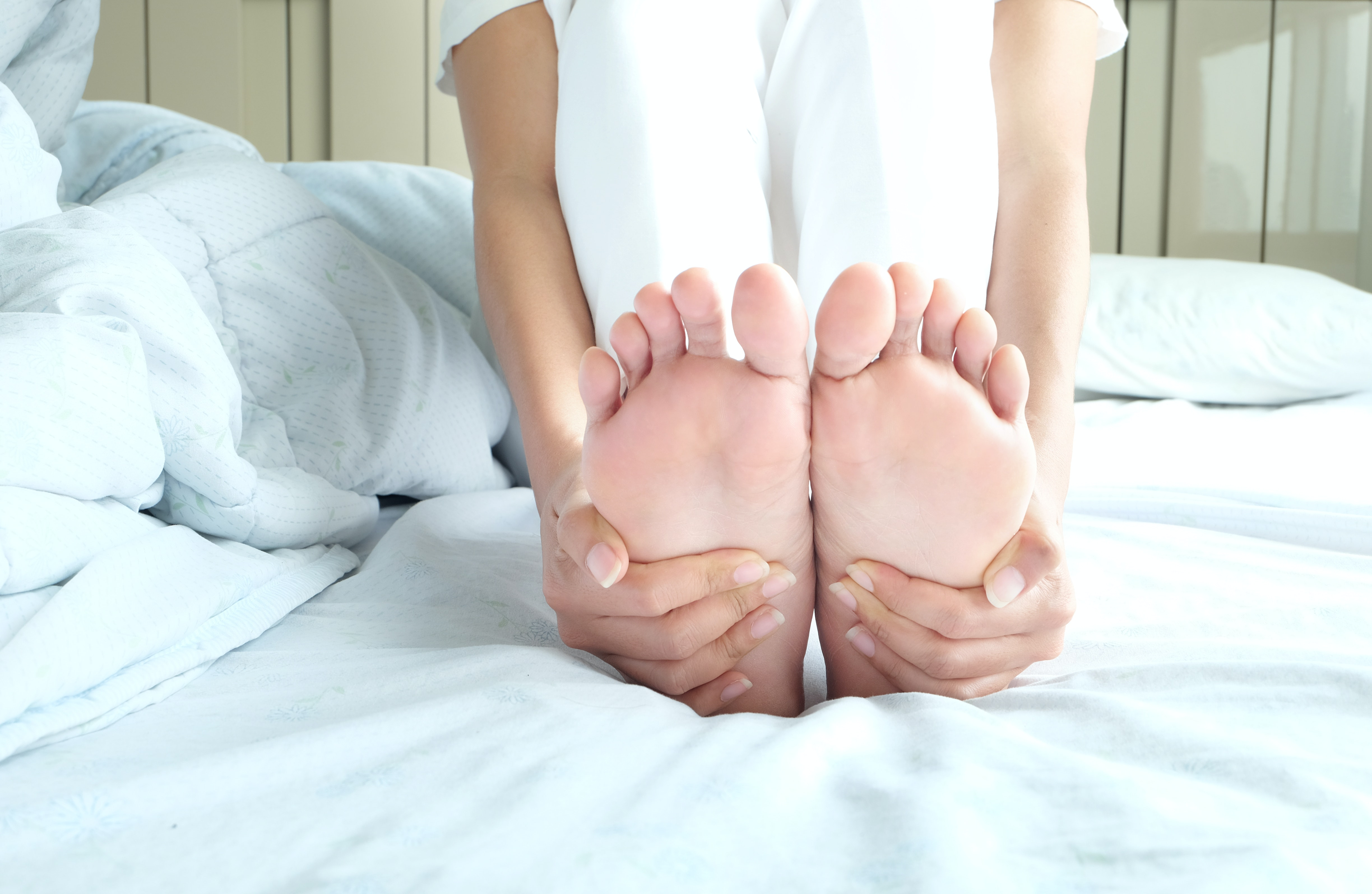 An image depicting a person suffering from pain in the sole of the foot symptoms