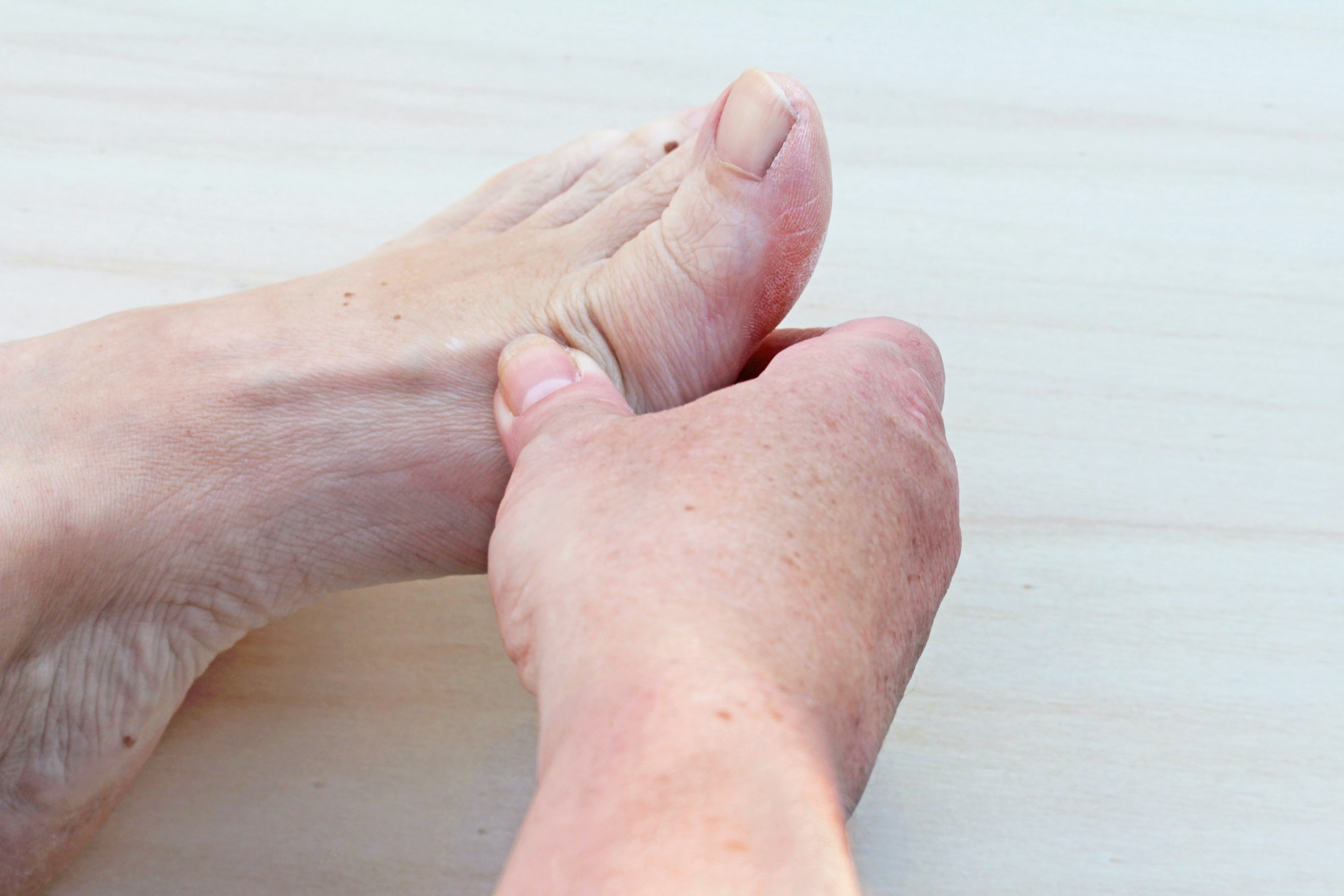 An image depicting a person suffering from painful foot lump symptoms