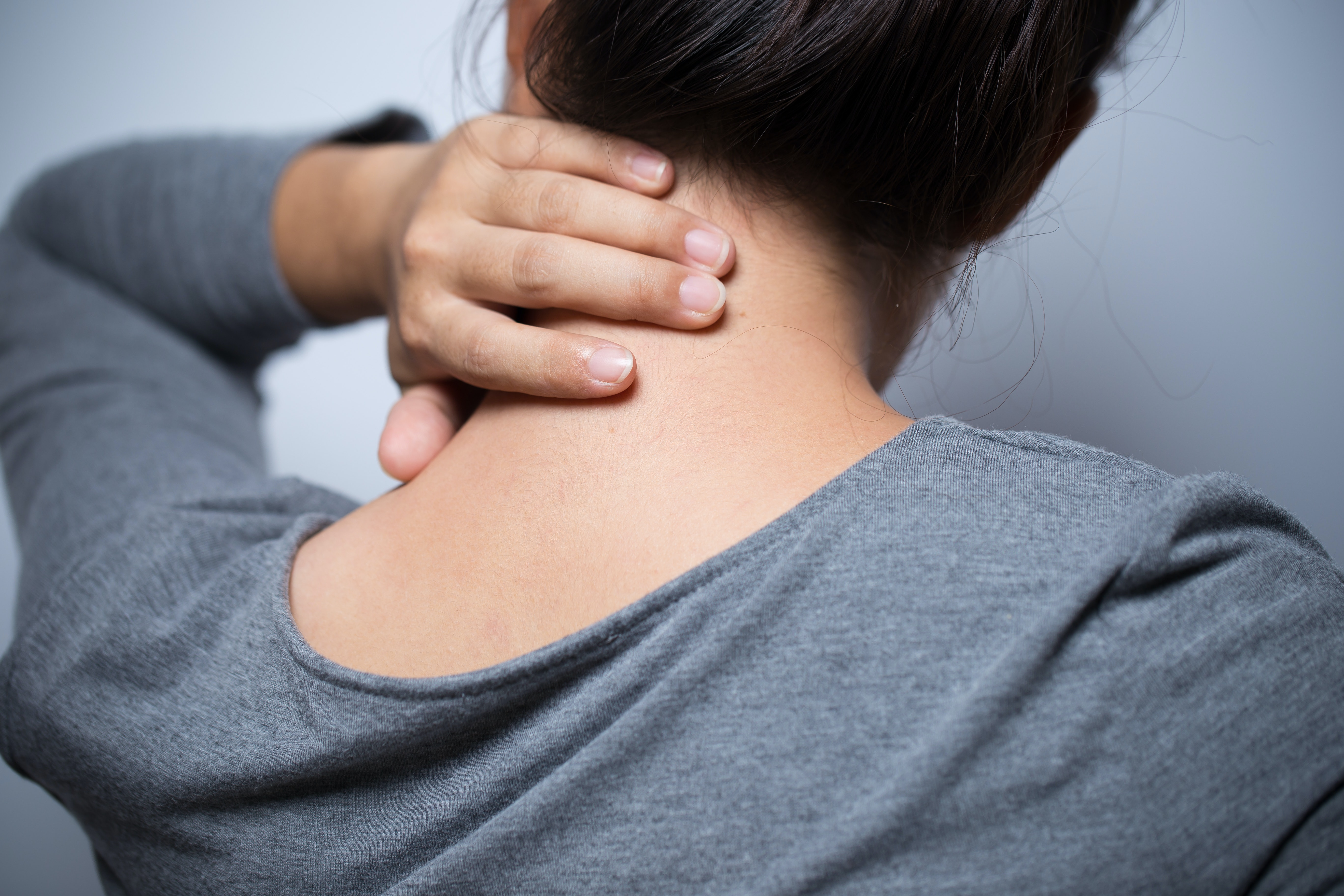 An image depicting a person suffering from painful neck lump symptoms