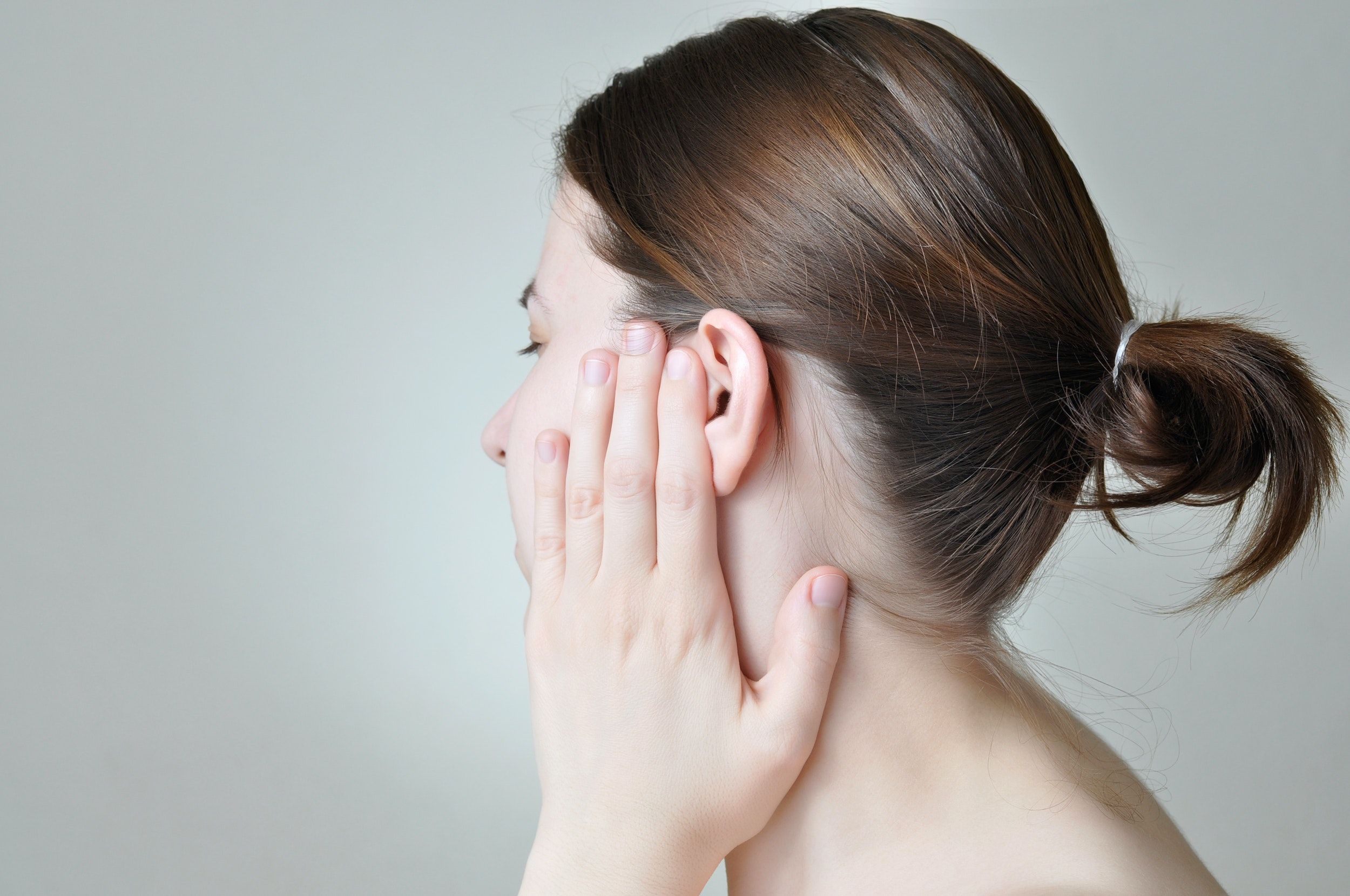 An image depicting a person suffering from ringing in the ears symptoms