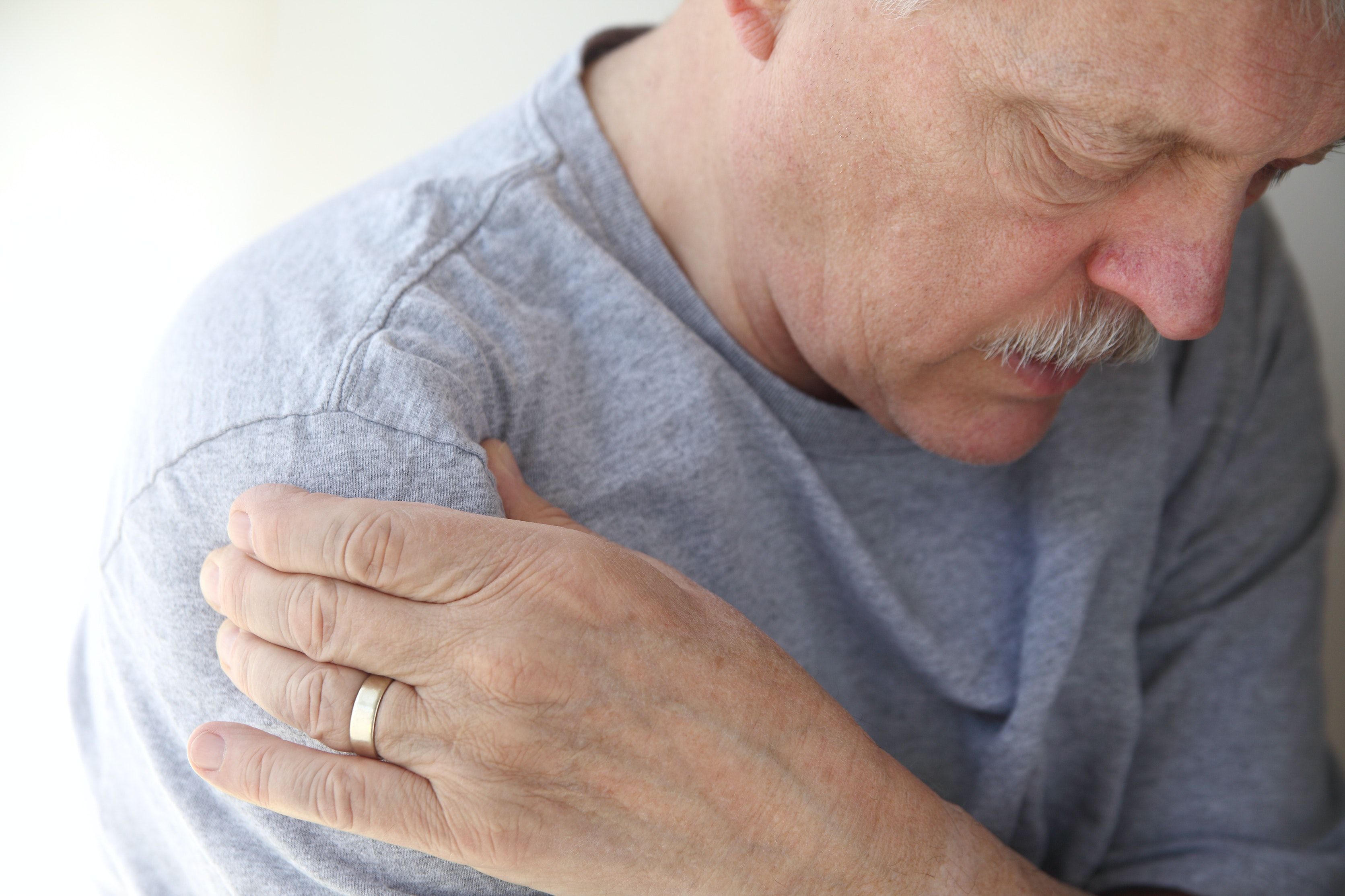 An image depicting a person suffering from shoulder weakness symptoms