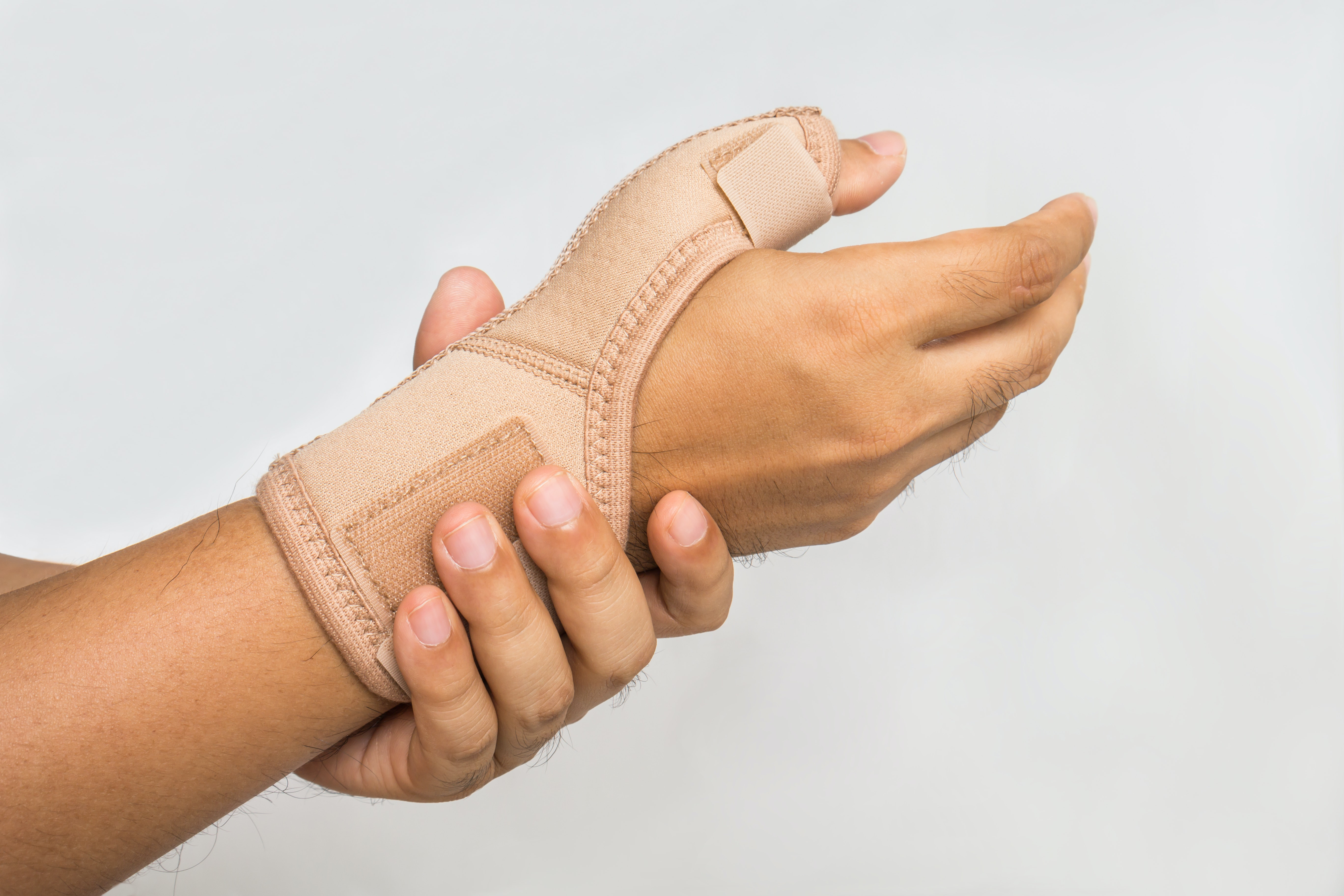 An image depicting a person suffering from Sprained Thumb symptoms