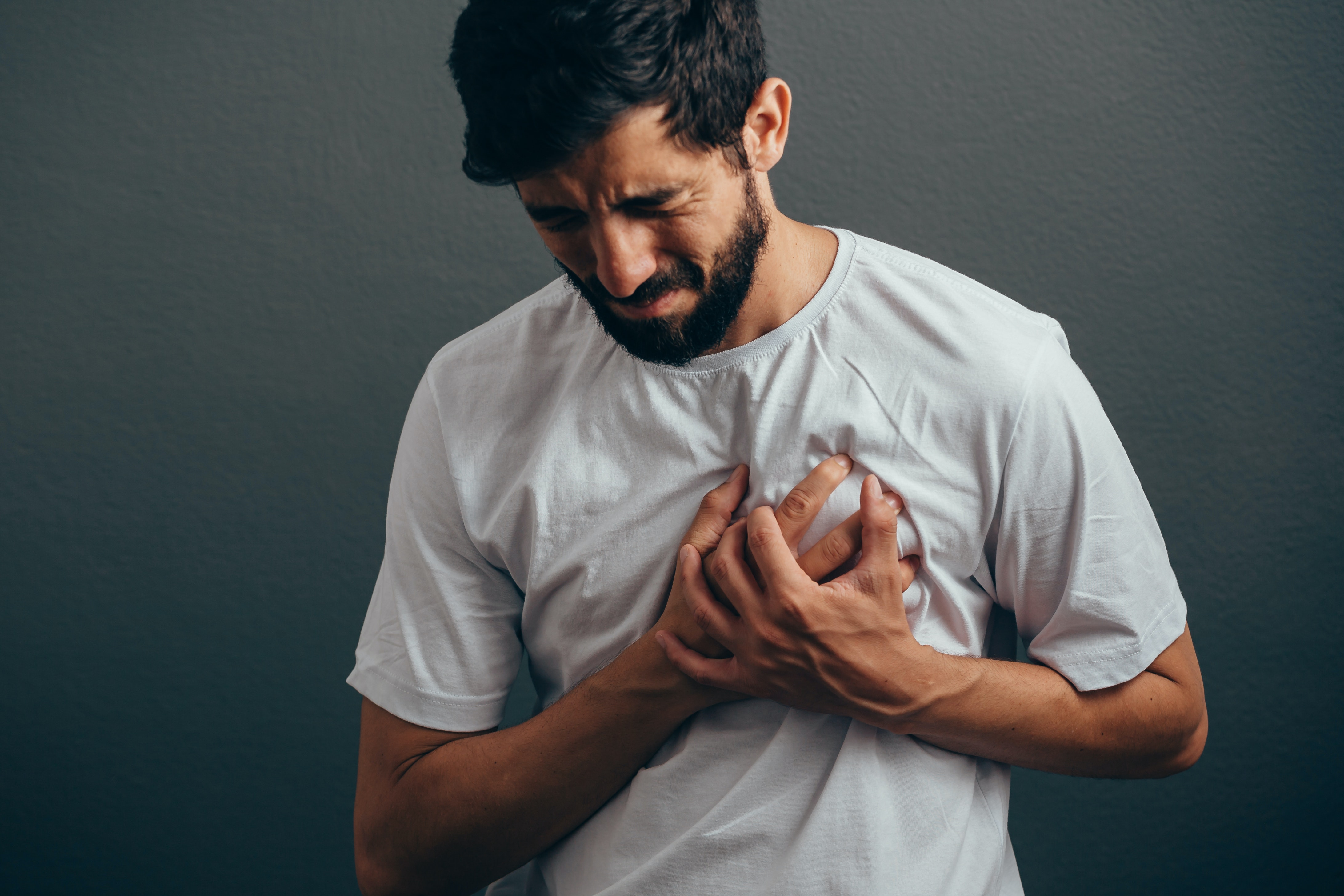 An image depicting a person suffering from tight, heavy, squeezing chest pain symptoms