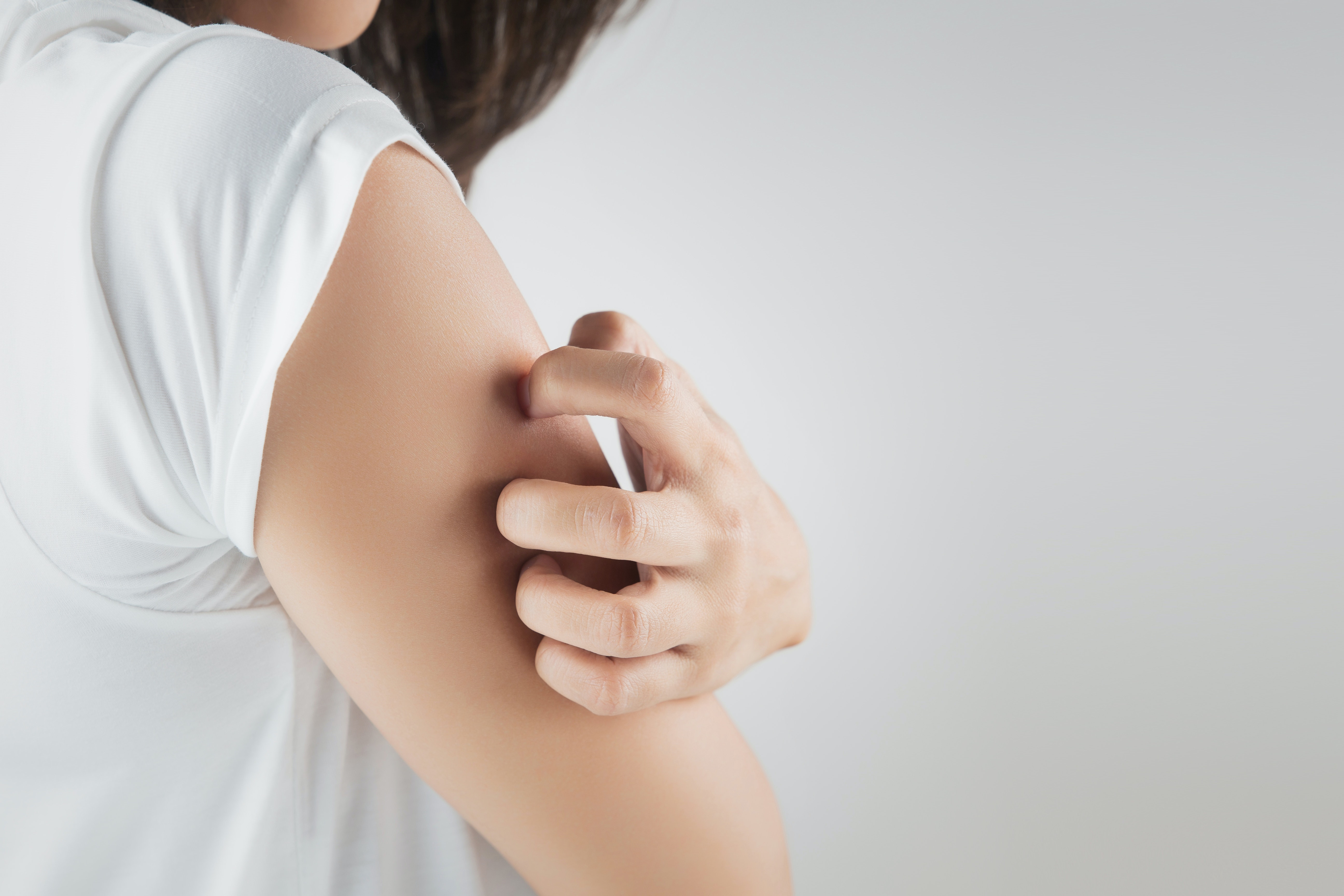 An image depicting a person suffering from upper arm itch symptoms