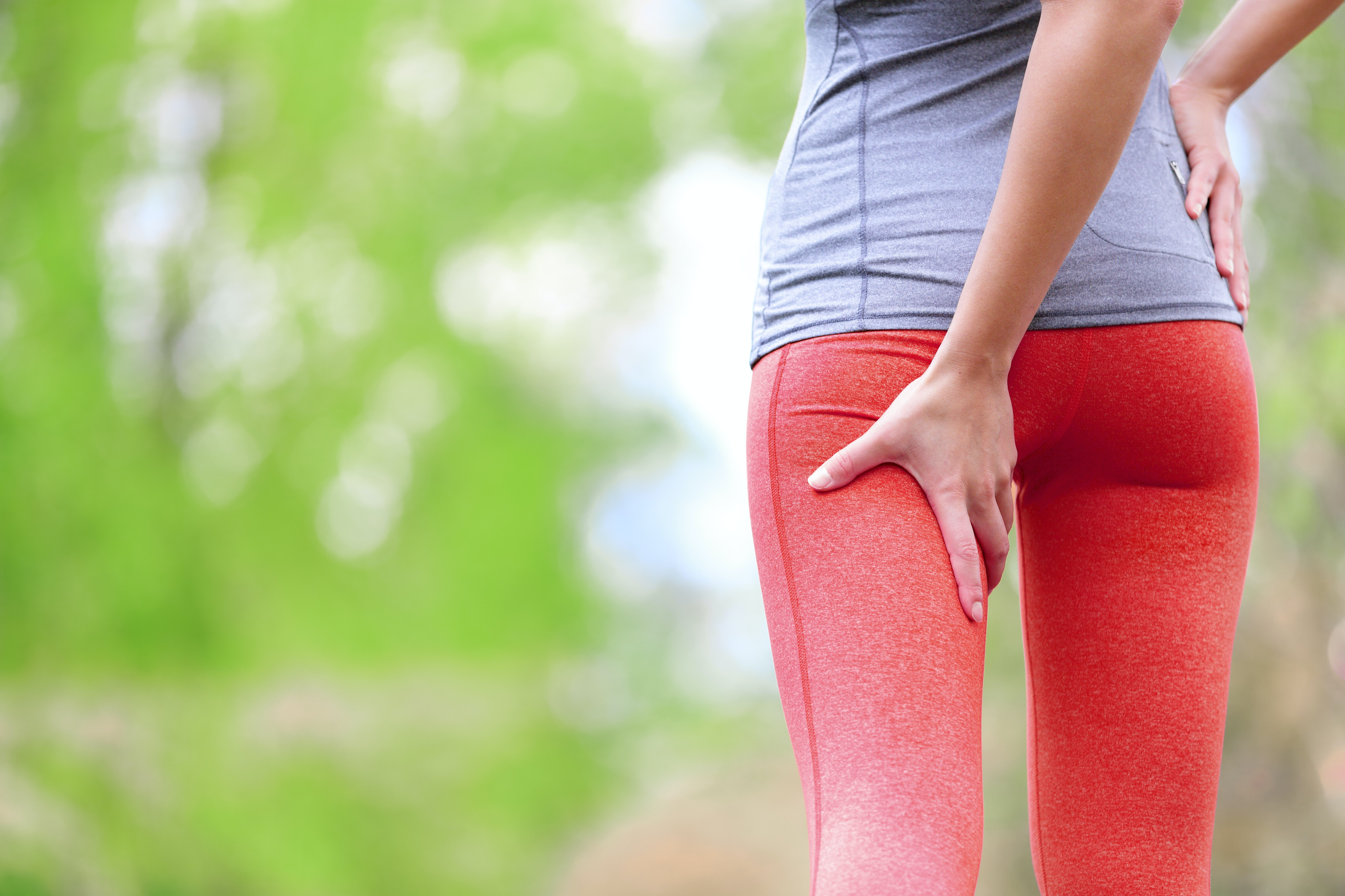 An image depicting a person suffering from upper leg pain symptoms