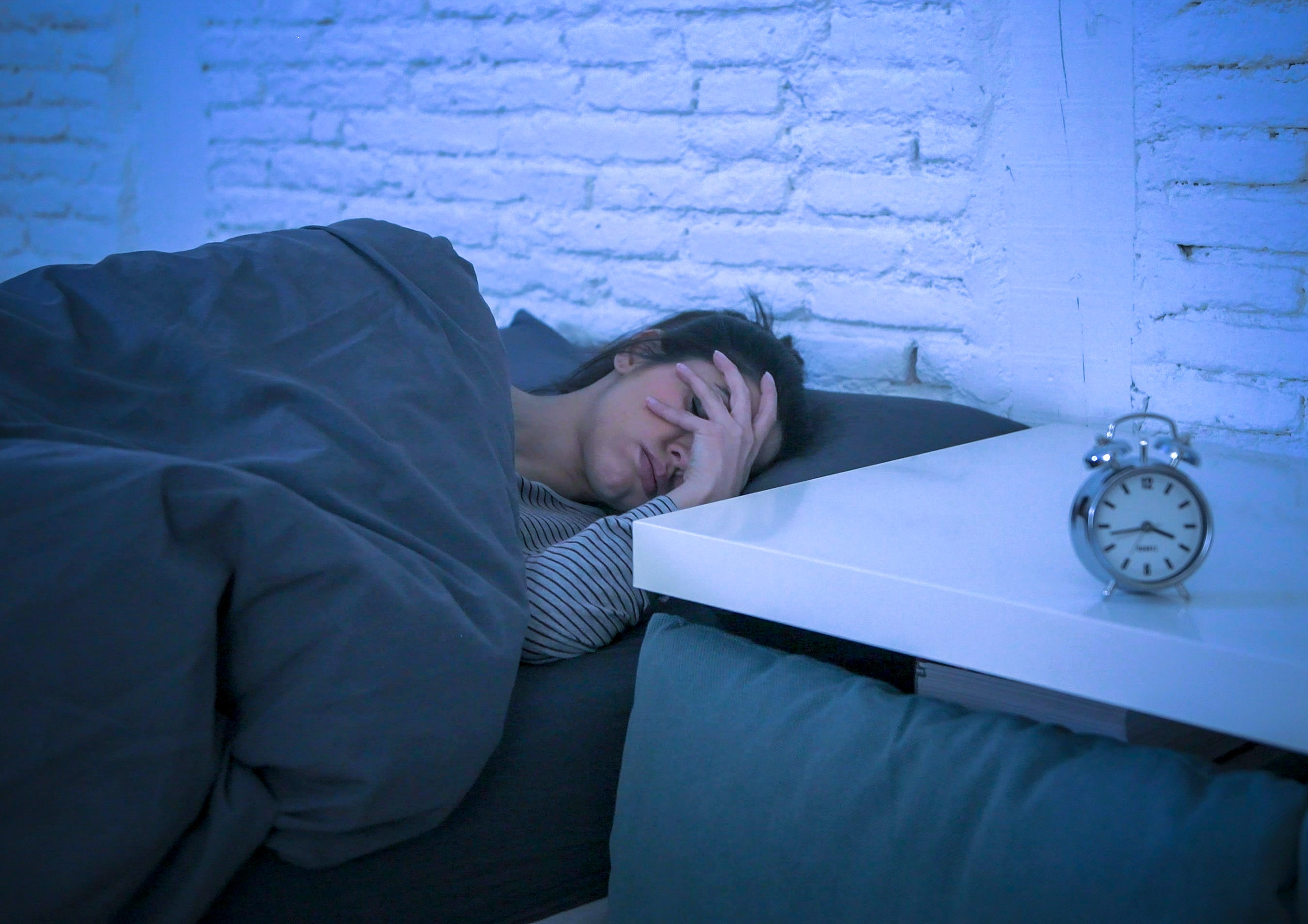 An image depicting a person suffering from waking up regularly to pee at night symptoms