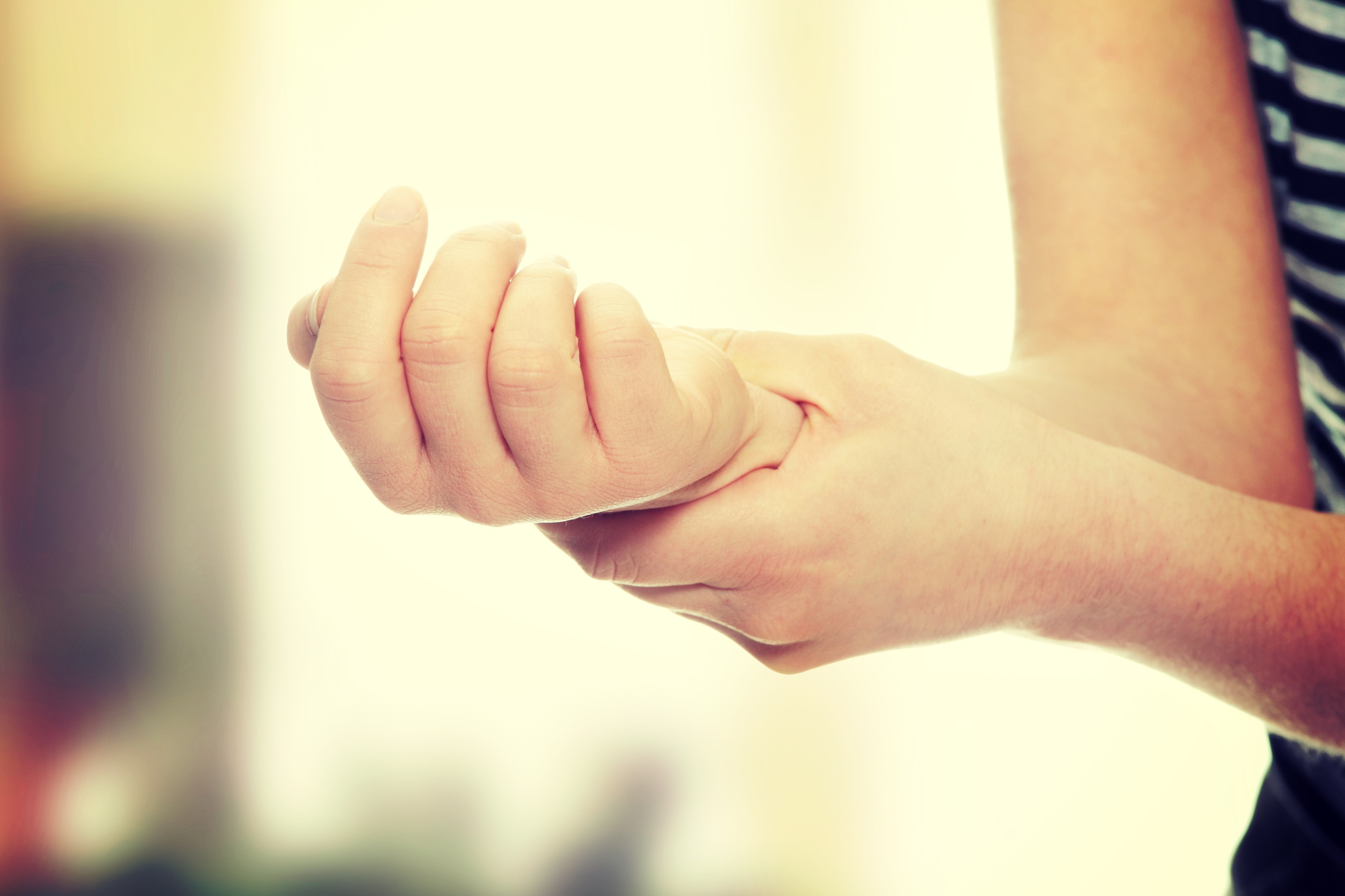 An image depicting a person suffering from wrist sprain symptoms
